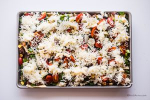shredded mozzarella cheese sprinkled on top of the fresh veggies on the sheet pan