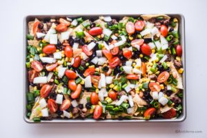 sliced veggie toppings spread evenly over tortilla chips on the sheet pan