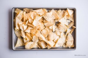 tortilla chips laid on to a baking sheet