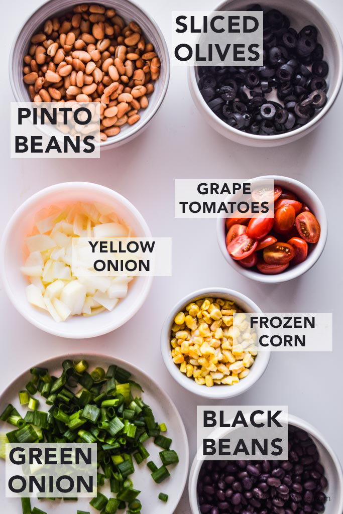 ingredients for sheet pan nachos in white bowls. Pinto beans, sliced olives, yellow onions, grape tomatoes, frozen corn, black beans and green onion
