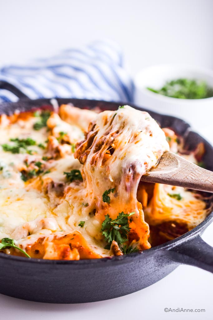 wooden spoon pulling up melted cheese from lasagna in skillet