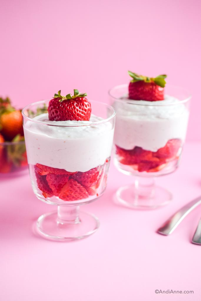 two strawberries and cream desserts in glasses with two spoons beside and a pink background