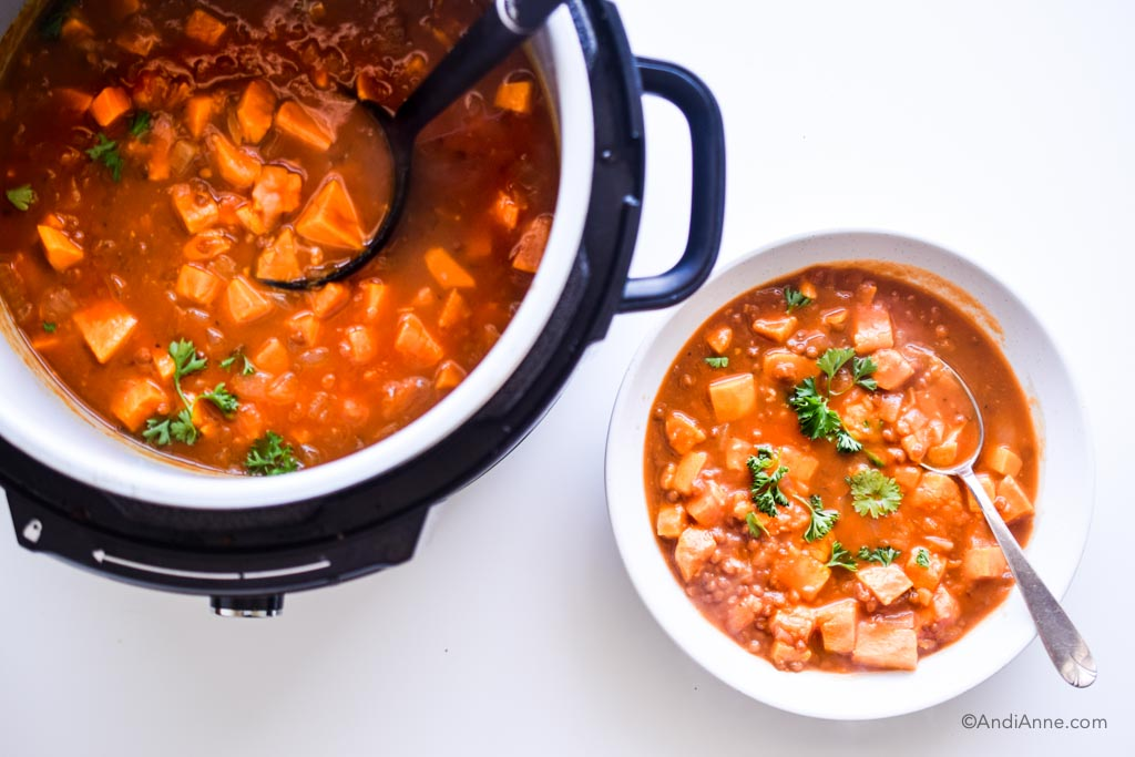 sweet potato lentil pumpkin soup in an instant pot with soup in a white bowl and spoon beside it