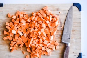 chopped sweet potato on a cutting board with a knife