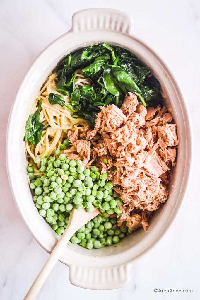 spinach, canned tuna, noodles, frozen peas inside a white bowl with a wooden spoon