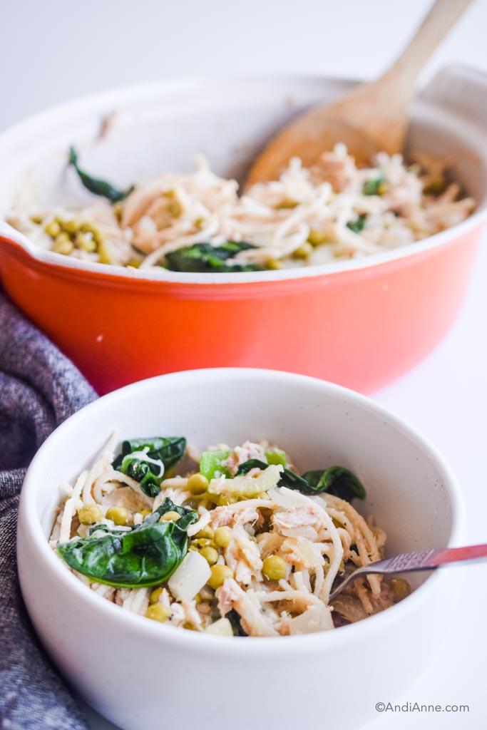 tuna noodle casserole in a white bowl with orange casserole dish in the background