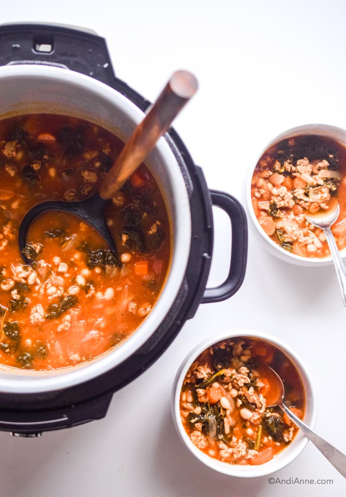 Ground turkey soup with kale and beans in a pressure cooker with wooden spoon and two white bowls of soup beside it