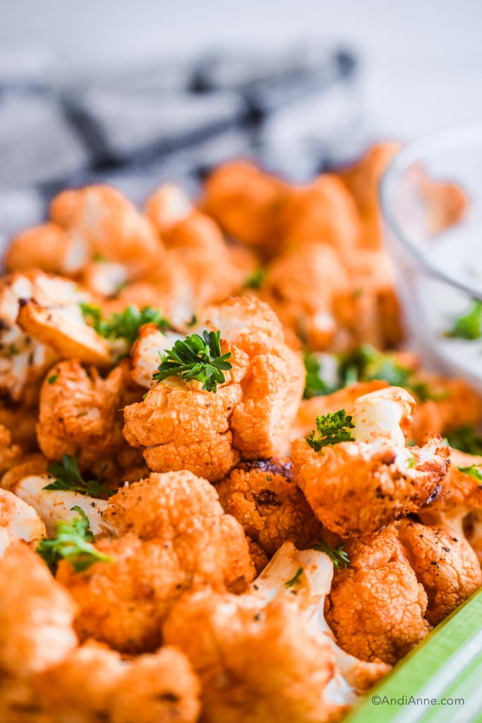 close up of air fryer buffalo cauliflower bites and bits of chopped parsley