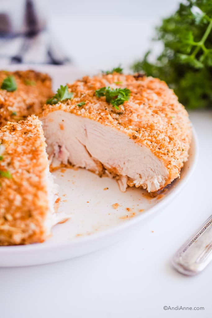 air fryer parmesan chicken breast cut open and detail of the cooked white chicken on the inside