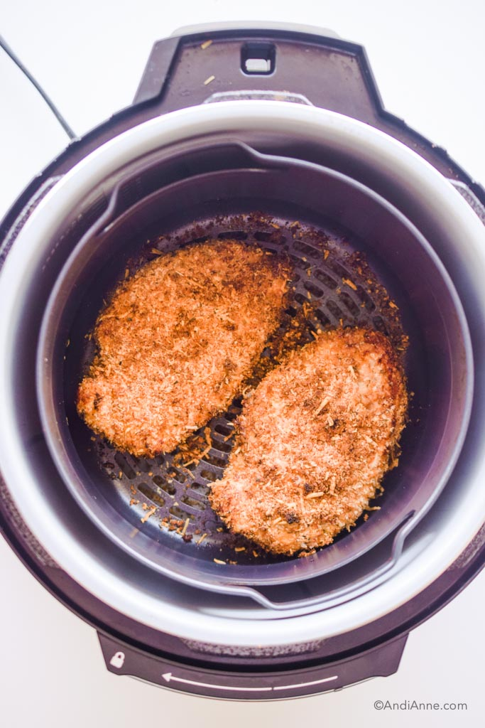 looking into an air fryer with cooked parmesan chicken breasts inside