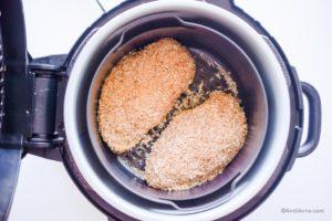 raw parmesan chicken breasts inside an air fryer