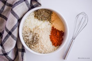 spices in a white bowl with for beside it