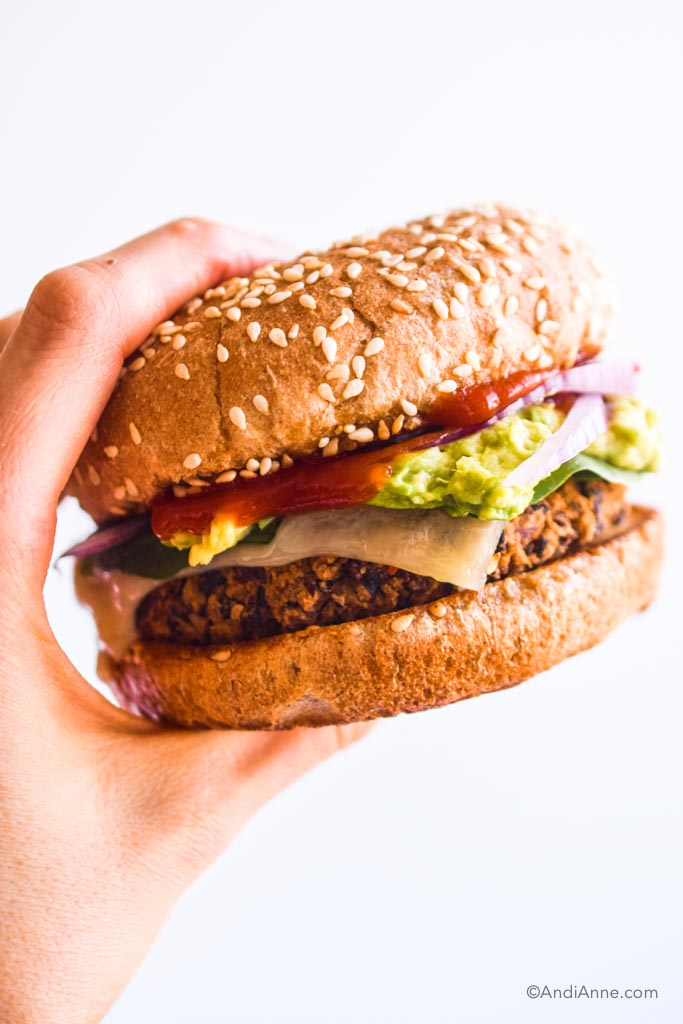 hand holding a black bean burger with ketchup, avocado, sliced onion and melted cheese