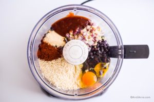 all ingredients including eggs, beans, barbecue sauce, spices and panko crumbs inside a food processor