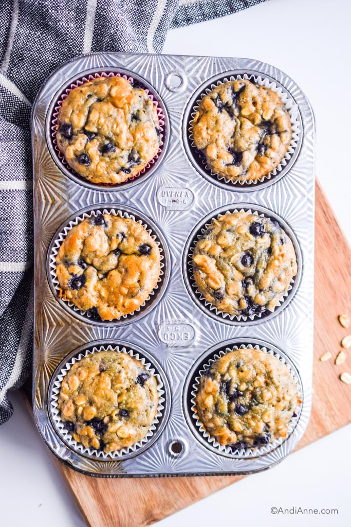 blueberry muffins in a muffin pan on top of a wood cutting board