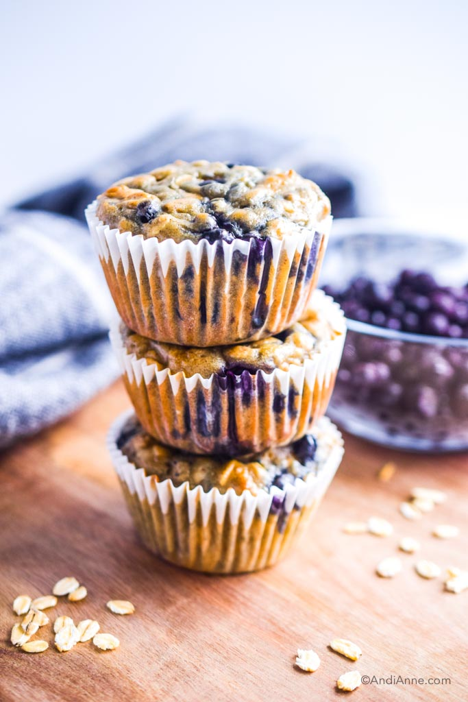 blueberry yogurt oat muffins stacked on top of eachother with a bowl of frozen blueberries and kitchen napkin in the background