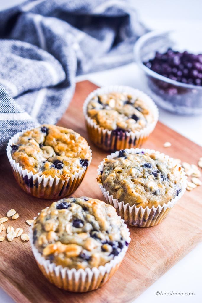 oatmeal muffins on a cutting board with napkin and frozen blueberries in the background