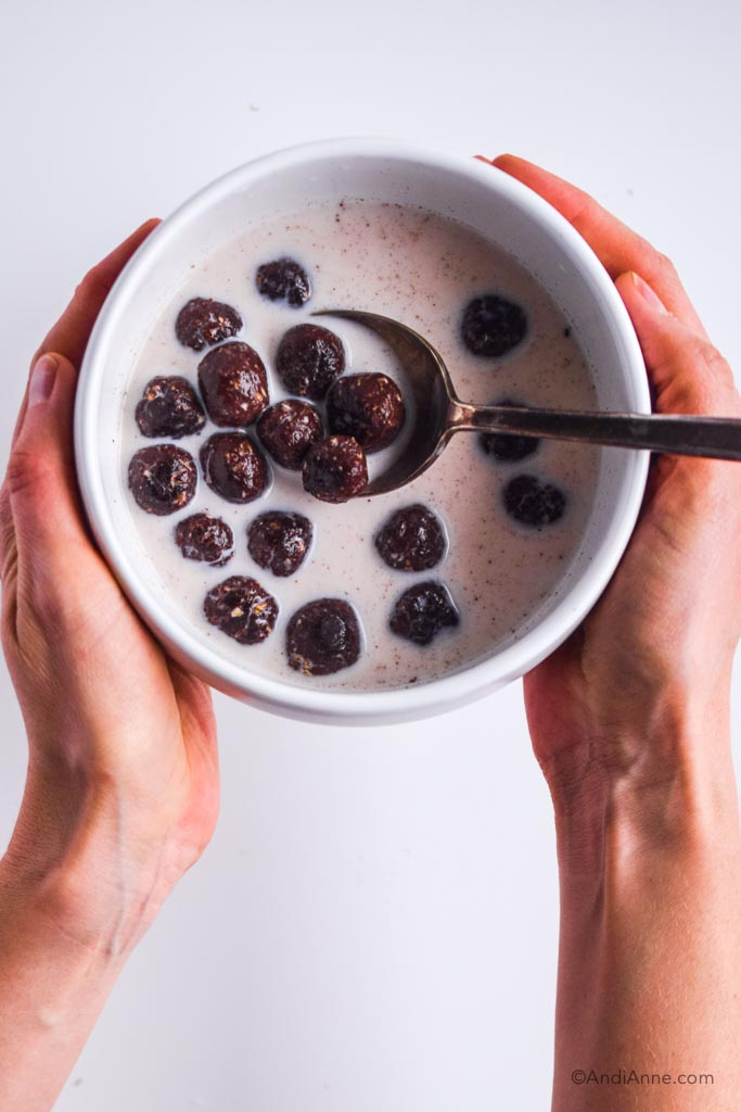 homemade chocolate cereal balls with milk in a white bowl with spoon held in hands