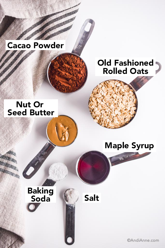 ingredients in measuring cups on a white table with kitchen towel. Cacao powder, rolled oats, nut butter, maple syrup, baking soda and salt.