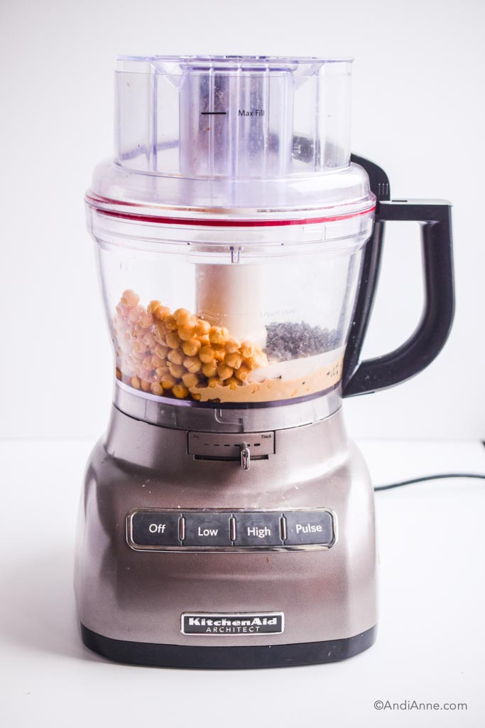 chickpeas, chocolate chips, tahini and other ingredients in a KitchenAid food processor with grey base and black handle.