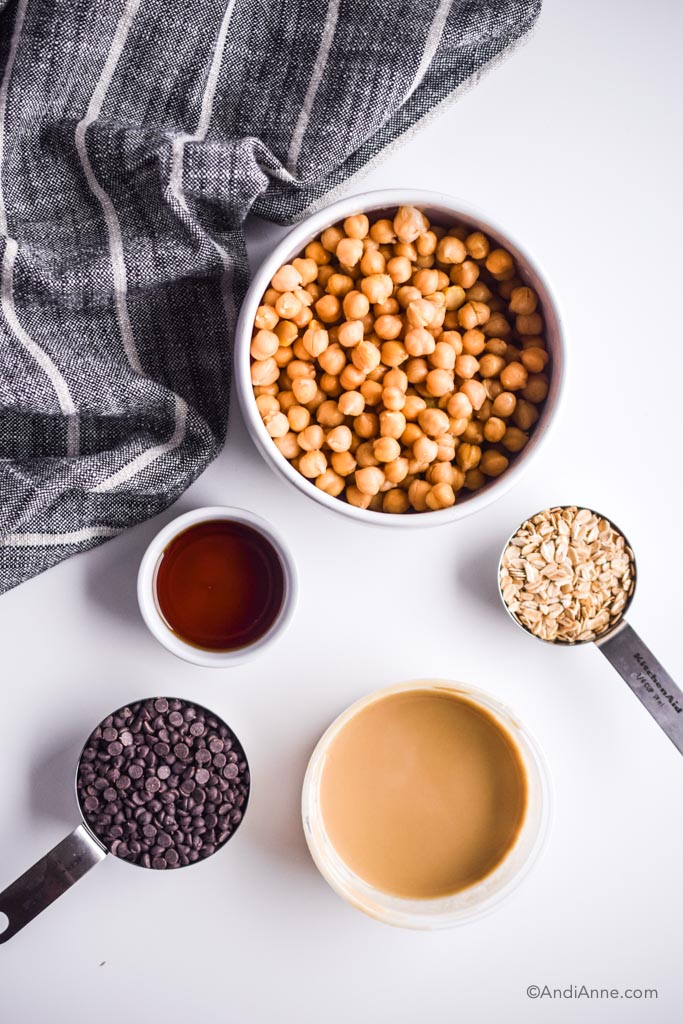 Bowl of chickpeas, and cups of rolled oats, maple syrup, tahini and chocolate chips on a white table with black and white kitchen napkin.