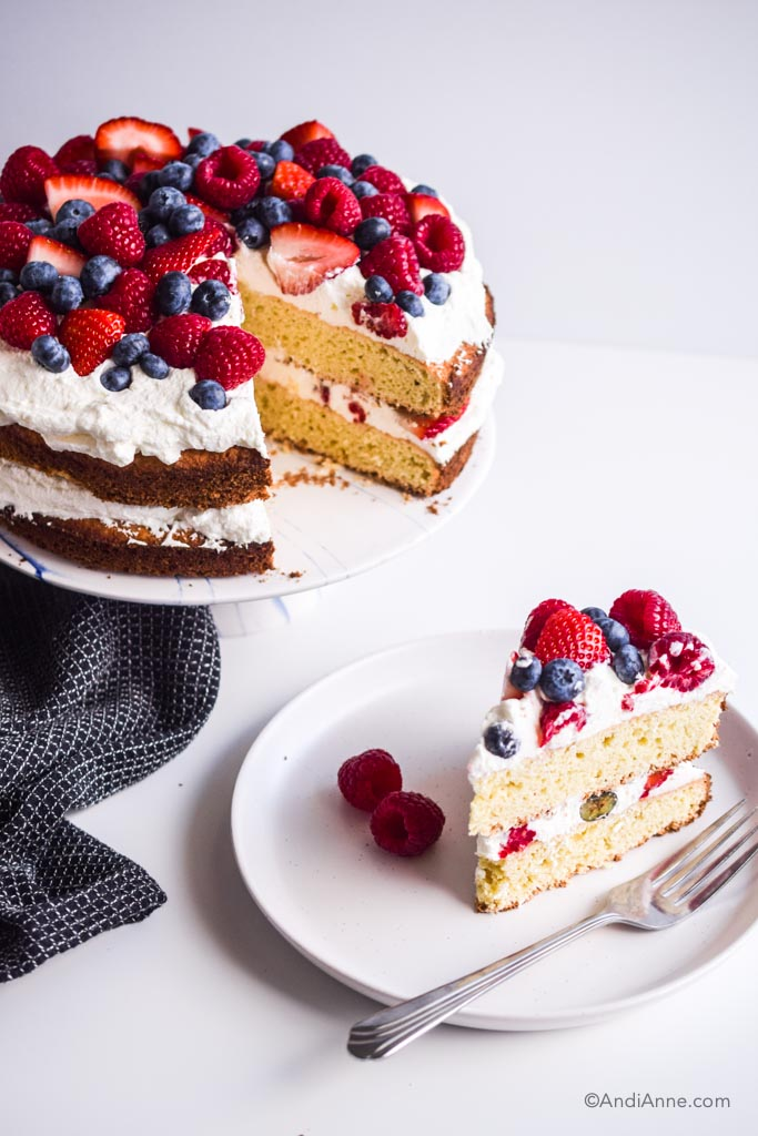 slice of cake on a white plate with fork beside cake stand with full cake and black kitchen towel