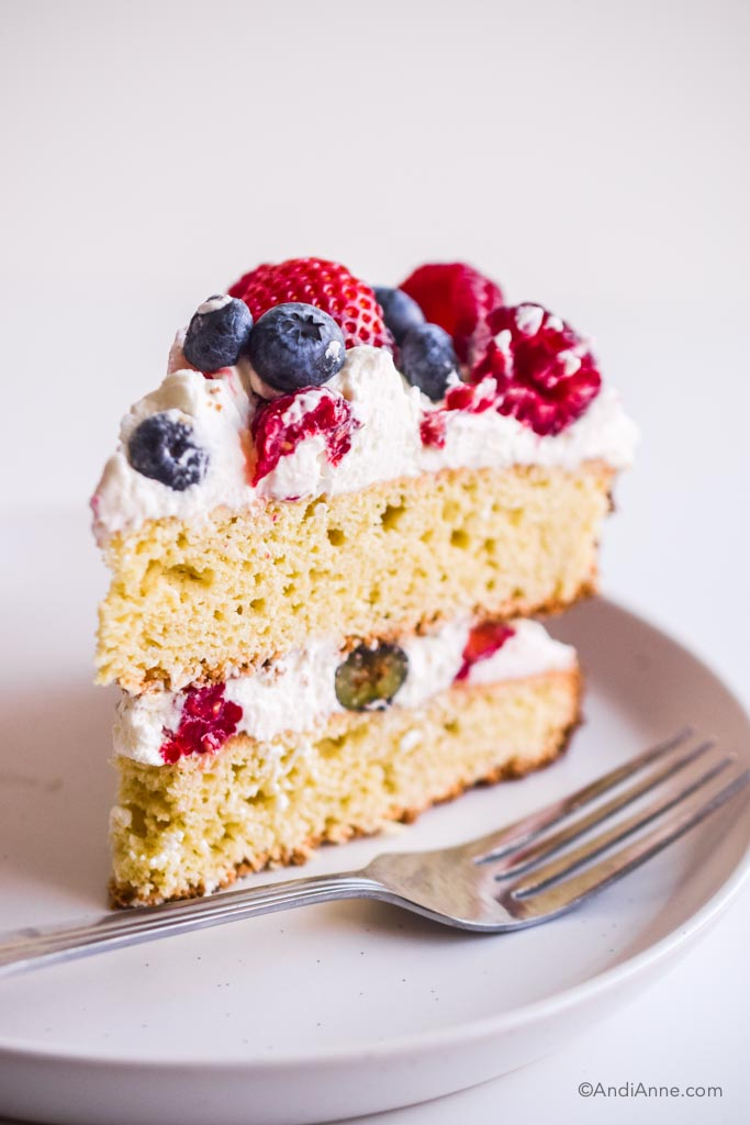 slice of gluten free white cake with whipped cream and berries in the center and on top