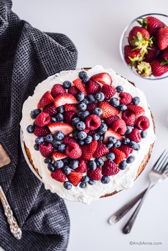 fresh berries on top of whipped cream with black kitchen towel, a glass bowl of strawberries and two forks