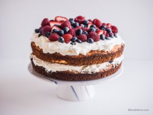 gluten free cake with whipping cream and fresh berries piled on top