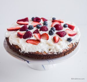 whipping cream and sliced berries on a single layer of cake