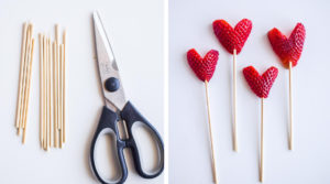 scissors, cut wooden skewers and heart shaped strawberries with skewers poked through them