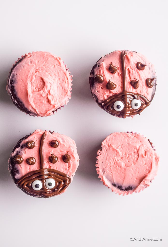 four chocolate cupcakes with pink icing. Two have ladybug decorations on top.