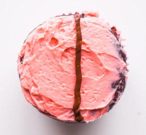 chocolate cupcake with pink icing and chocolate line drawn down the cetner
