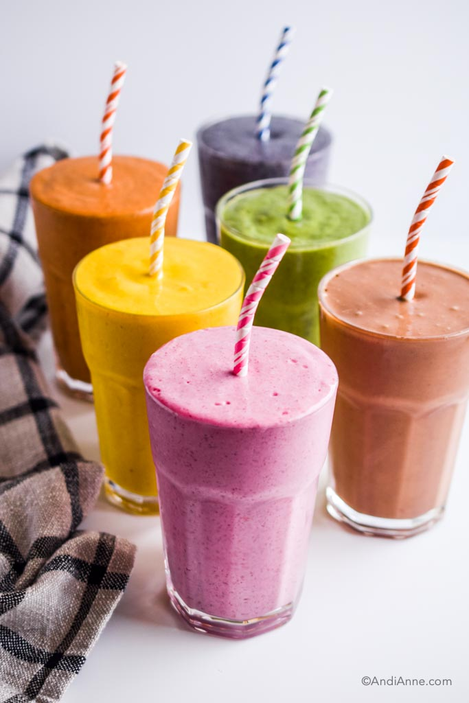 six colorful healthy smoothies in glasses with paper straws.