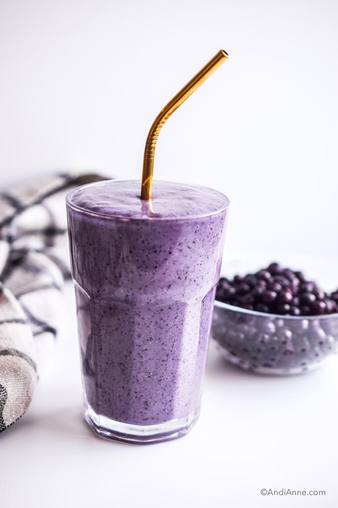 blueberry smoothie in a glass with metal straw and a bowl of blueberries behind it
