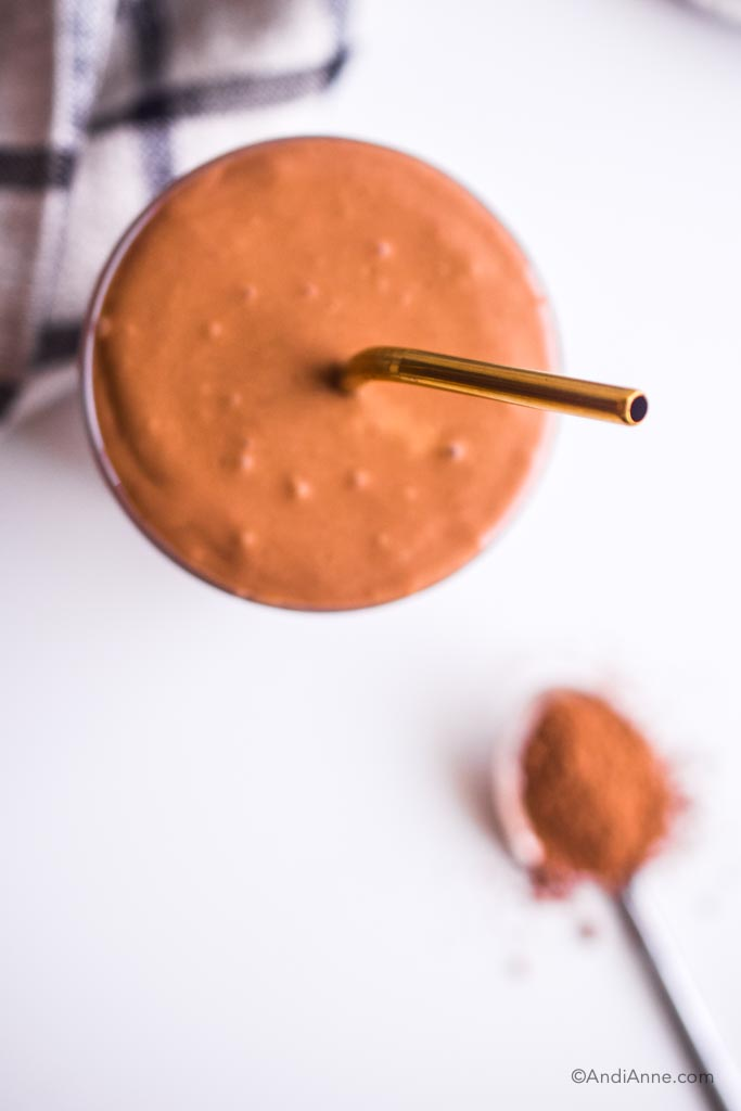 looking down on chocolate smoothie with gold straw. Spoon with cacao powder is blurred in the background.