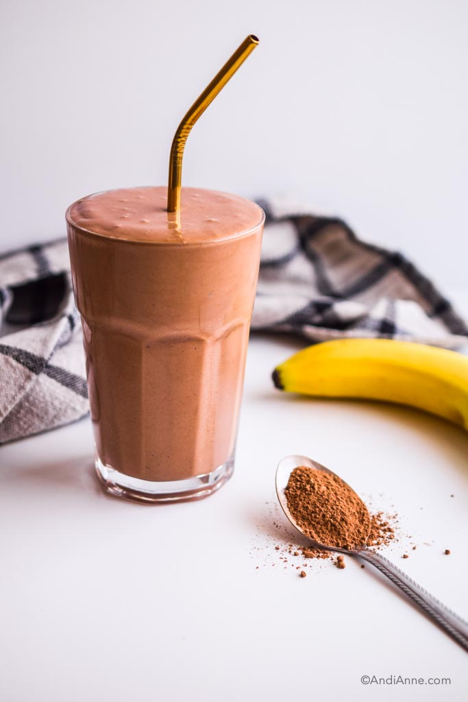 banana chocolate smoothie in a glass with gold straw. Kitchen napkin, banana and spoon of cacao powder surround it.