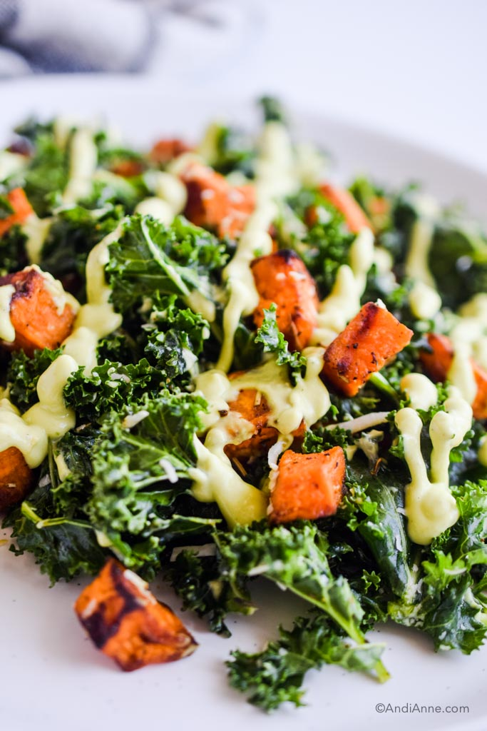close up of kale and roasted sweet potato drizzled with avocado dressing