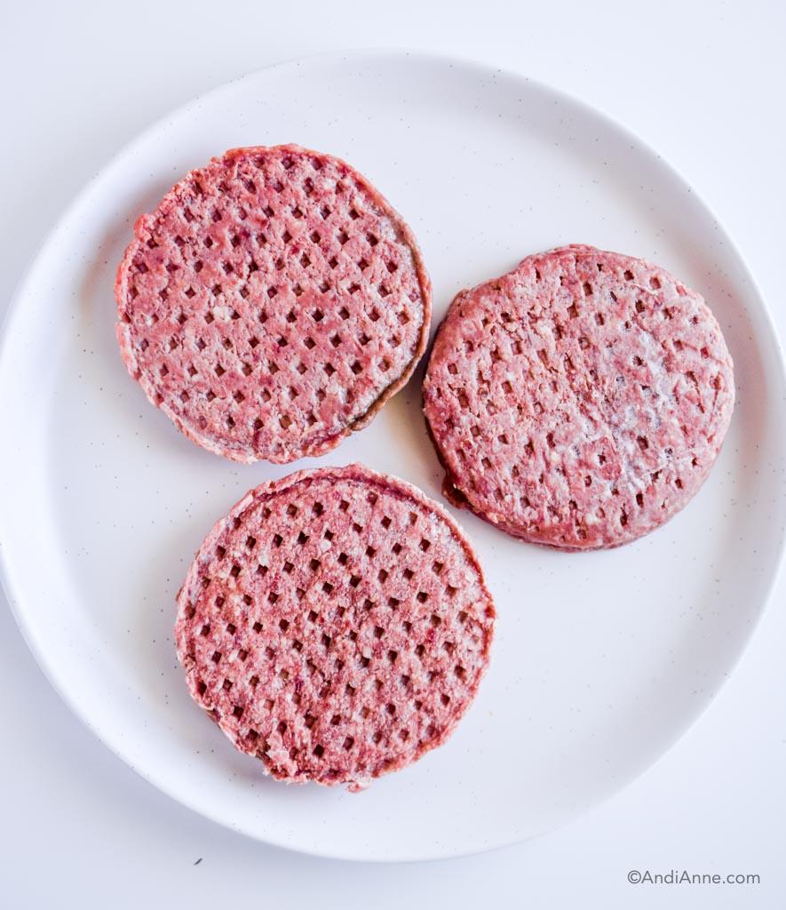 three raw hamburger patties on a white plate.