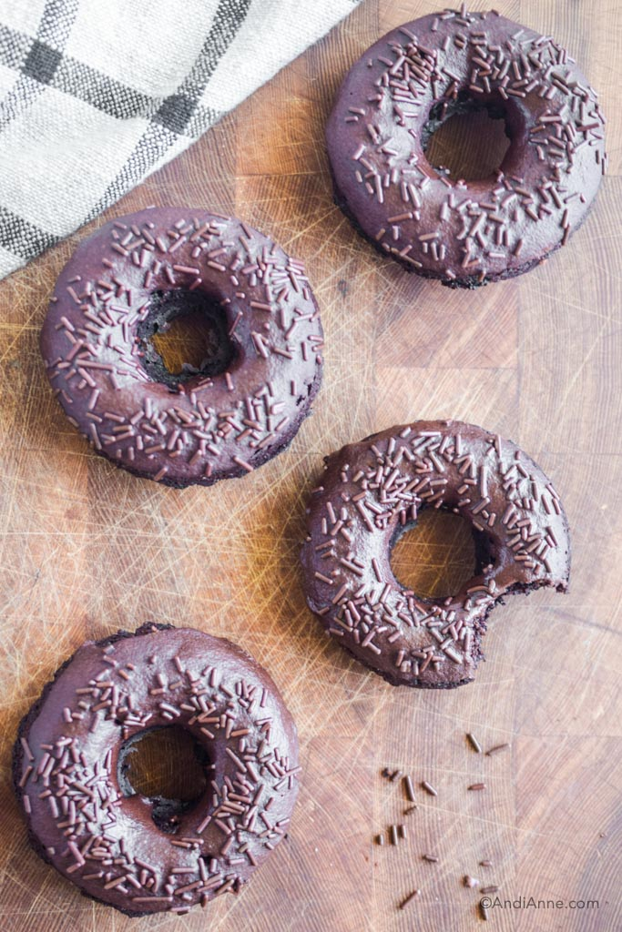 chocolate baked donuts with chocolate glaze and sprinkles on a wood cutting board.