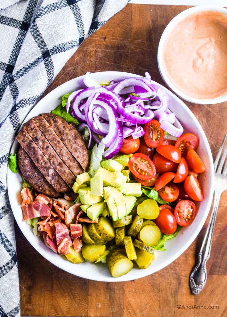 burger salad bowl on white plate with fork and kitchen towel beside it. Salad dressing in small bowl top right.