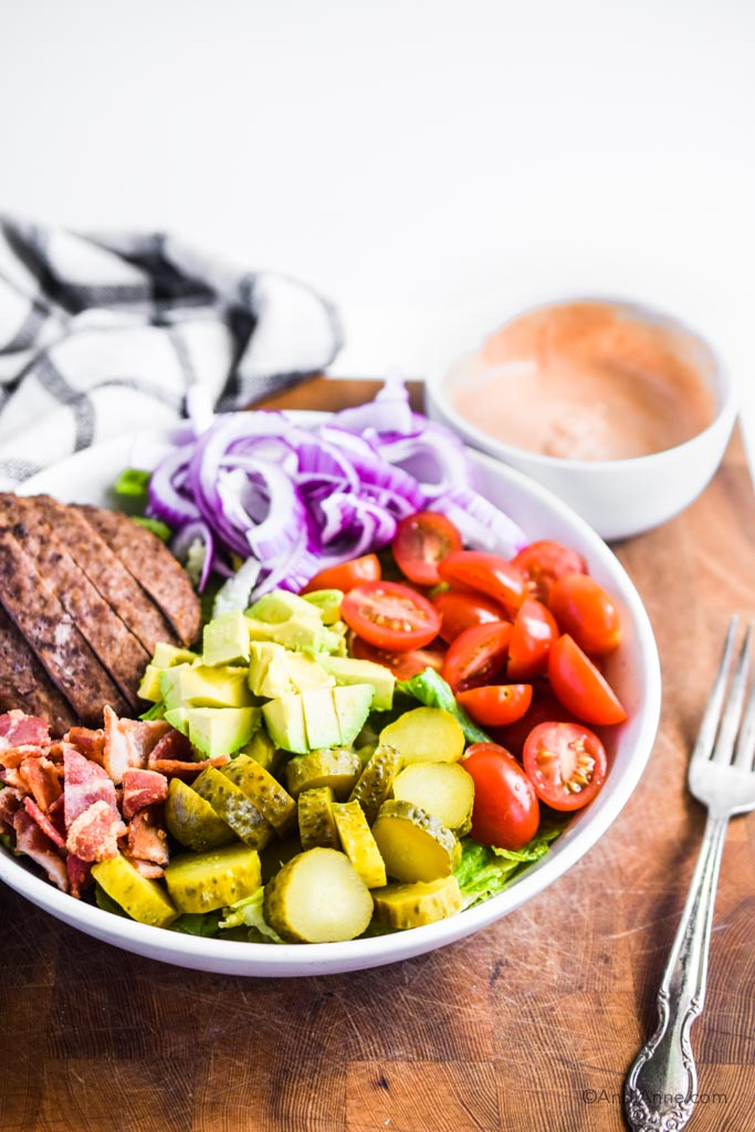 burger salad bowl with special sauce dressing in side bowl. forke and kitchen towel beside them
