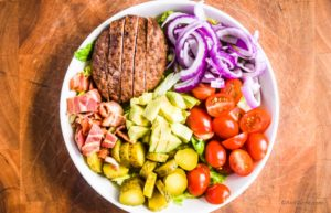burger salad bowl in a white dish on cutting board