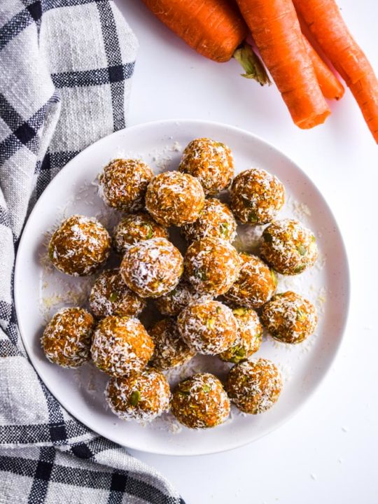 carrot cake bites on a white plate with raw carrots and a kitchen towel surrounding the plate.