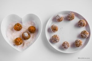 white heart shaped plate with shredded coconut and four energy balls beside a white circle plate and finished rolled carrot cake bites