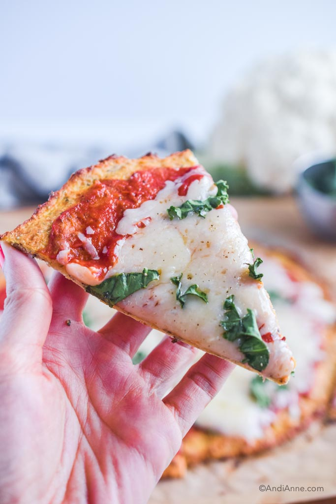 hand holding one slice of margherita pizza with cauliflower crust