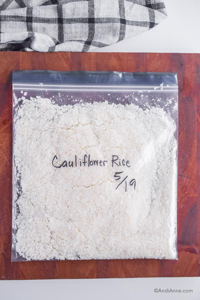 riced cauliflower in a freezer bag laying flat on a cutting board with name and date written on the front