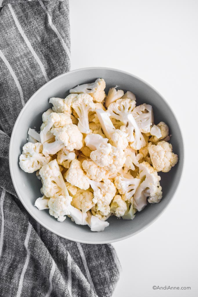 chopped cauliflower in a blue bowl with a striped kitchen towel beside it