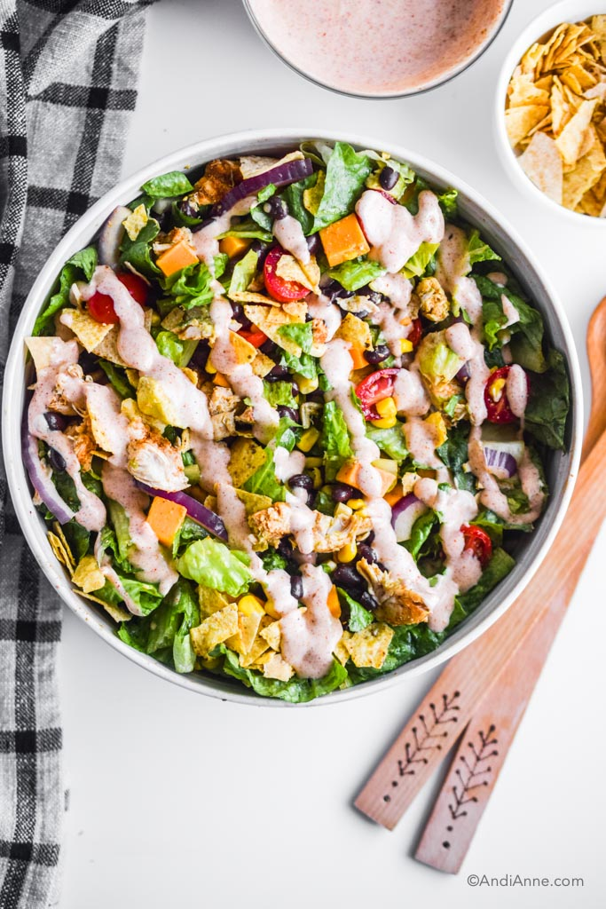 ranch taco chicken salad in a white bowl with kitchen towel and wooden spoons beside it.