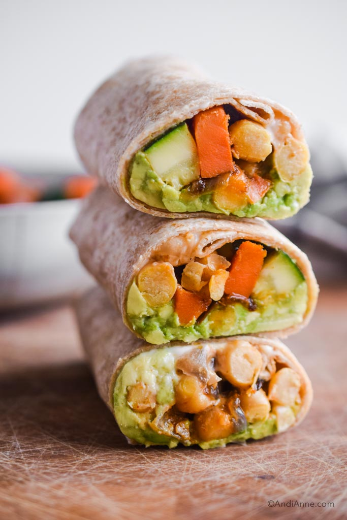 three chickpea zucchini stir fry wraps stacked on top of eachother.